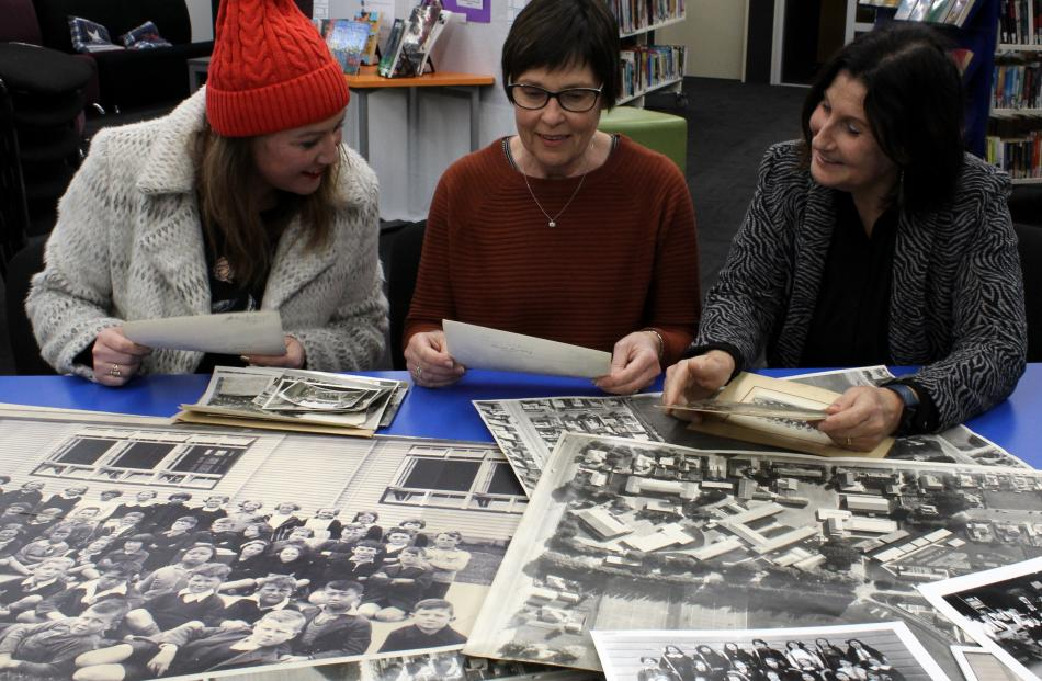 Poring over archive photos at the Taieri College library are Taieri College reunion committee...