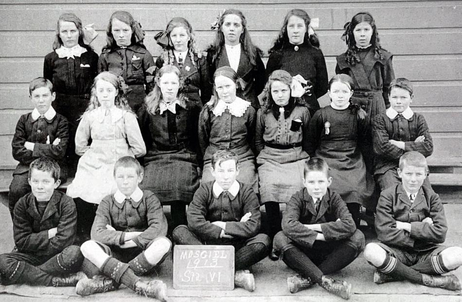 Boys and girls pose for a photo in 1913.