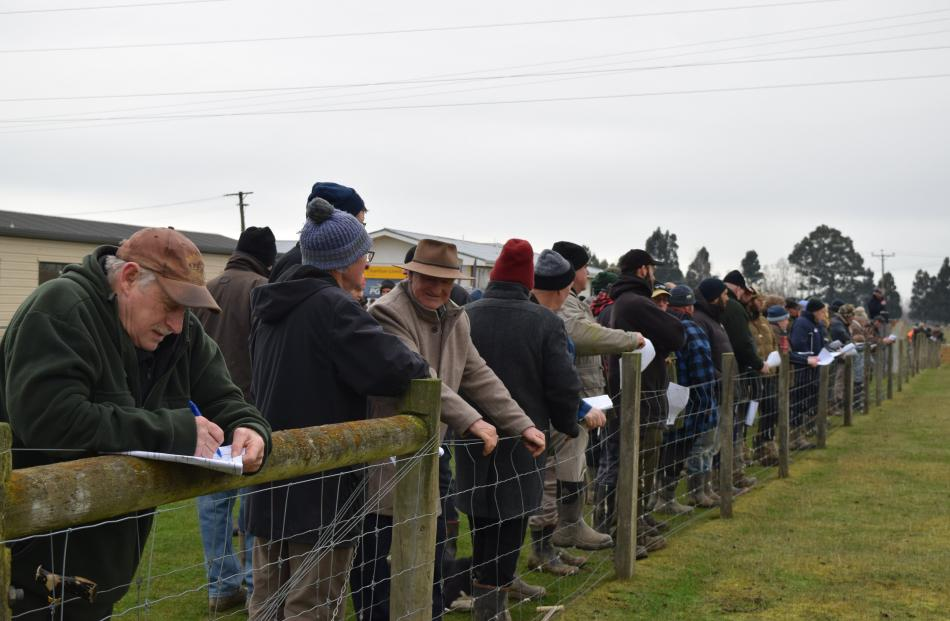 Peter Allison, of Waihola, writes a note in his catalogue among a crowd of more than 200 people...