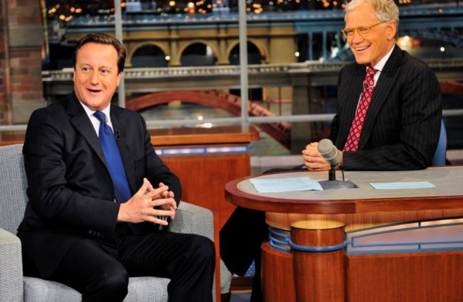 British Prime Minister David Cameron (L) talks with CBS Late Show host David Letterman during...