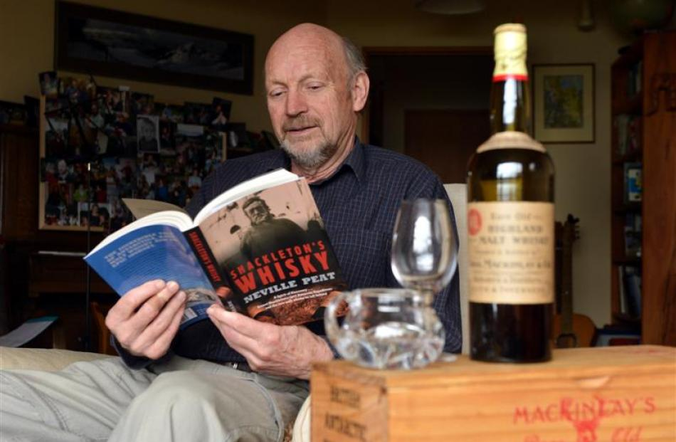Neville Peat with a copy of his book and a bottle of Mackinlay's whisky. Photo by Stephen Jaquiery.