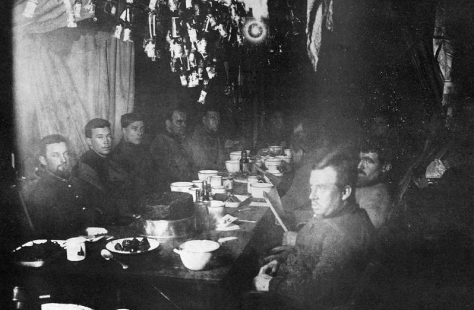 The midwinter feast at the Nimrod Hut, Cape Royds, in June 1908. Ernest Shackleton is at the head...