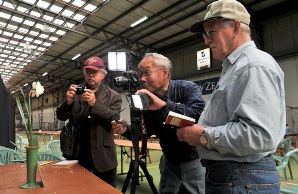Kirby Fong (centre) photographs a premier bloom while Don Catons (left) from the United States...