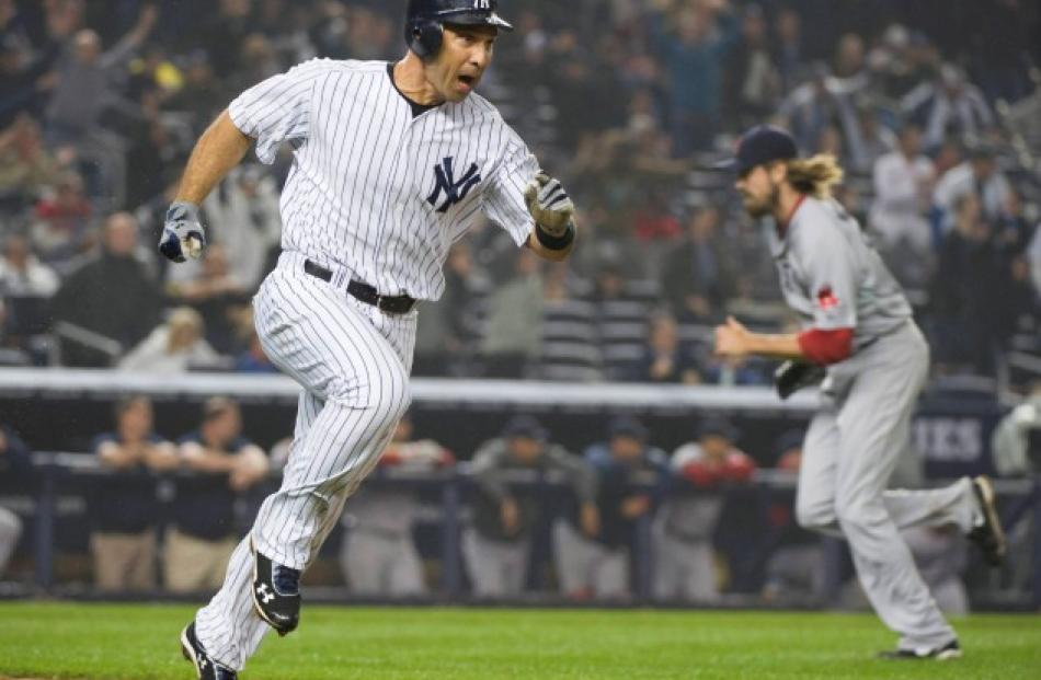 New York Yankees batter Raul Ibanez (L) celebrates after hitting a game-winning walk-off single...