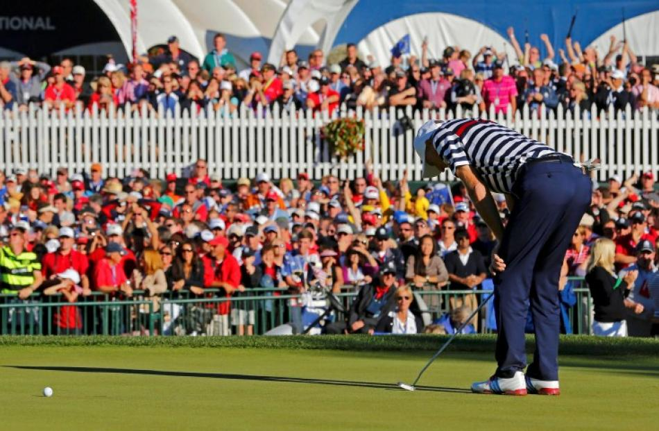 US golfer Jim Furyk reacts to missing a par putt on the 18th green to lose his match to Team...