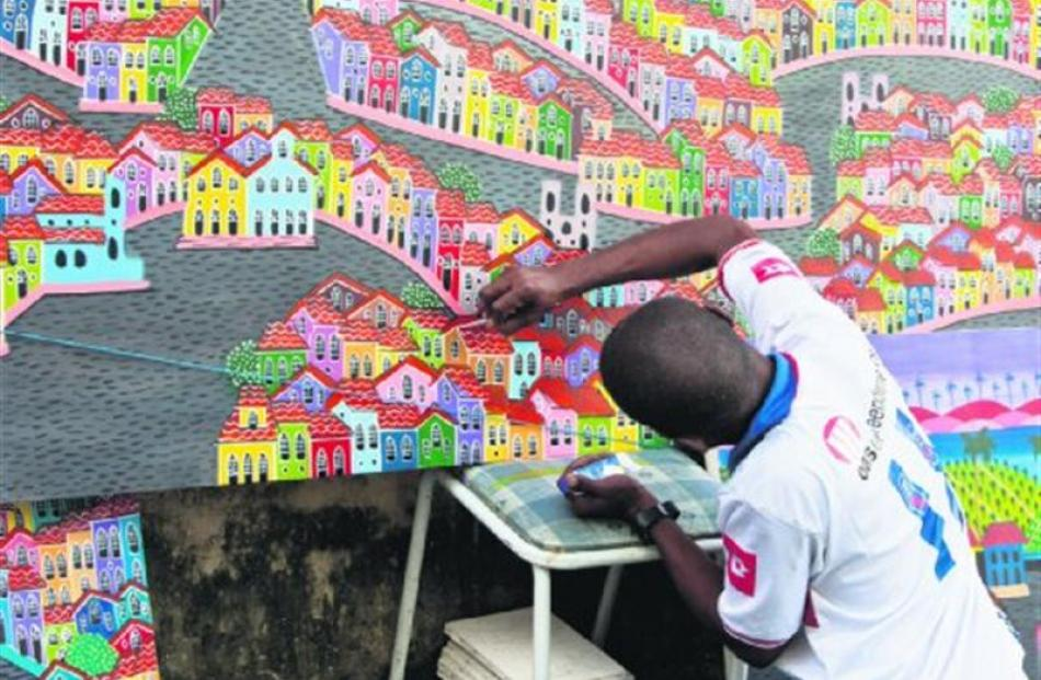 A young Salvadorean paints the brightly coloured facades of the old town.