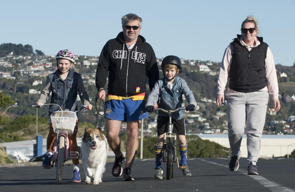 Out for their daily exercise at St Kilda Beach yesterday are (from left) Lily (9), Shaun, Malakai...