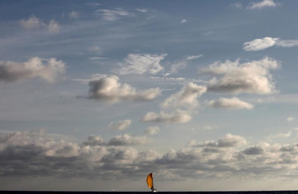 A sailboat competes at the fourth stage of the New Moon Regatta tournament off the coast of...