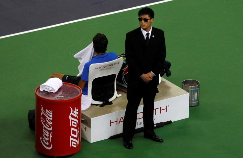 A security guard stands next to Switzerland's Roger Federer as he takes a break during his...