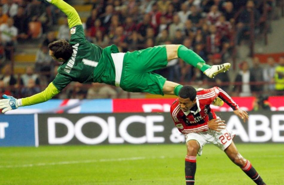 Inter Milan's goalkeeper Samir Handanovic (L) makes a save against AC Milan's Urby Emanuelson...