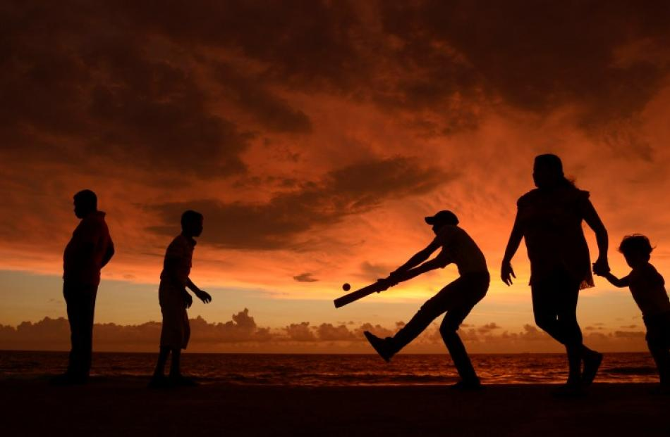 People play cricket as people walk along the seafront at Galle face green in Colombo before the...