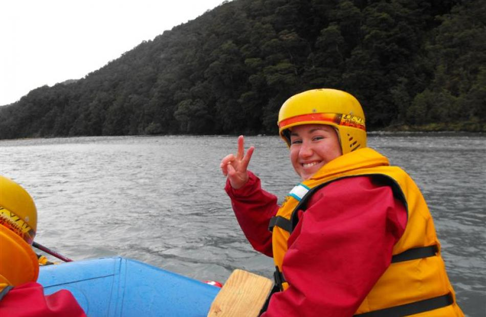 Olivia Caldwell, sporting a rafting helmet, enjoys her first experience of whitewater rafting.