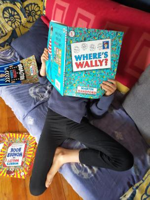 Emma Bristow (9) gets lost in Where's Wally books during lockdown. PHOTO: SUPPLIED