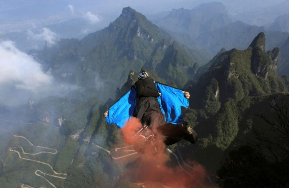A contestant flies during a World Wingsuit Championship at Tianmen Mountain in Hunan province,...