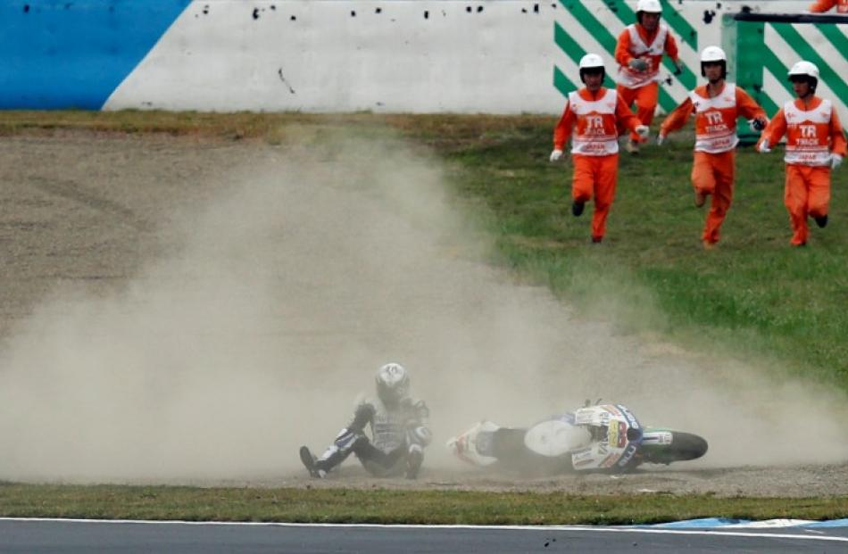 Course marshals run towards Colombian rider Yonny Hernandez after he fell off his motorcycle...