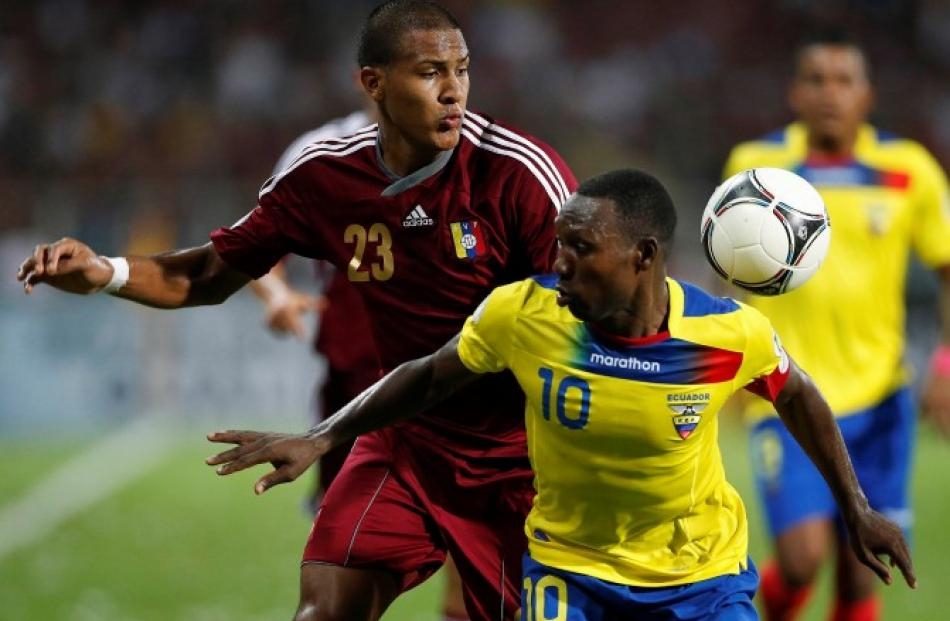 Ecuador's Walter Ayovi (R) and Venezuela's Jose Rondon challenge for the ball during their 2014...