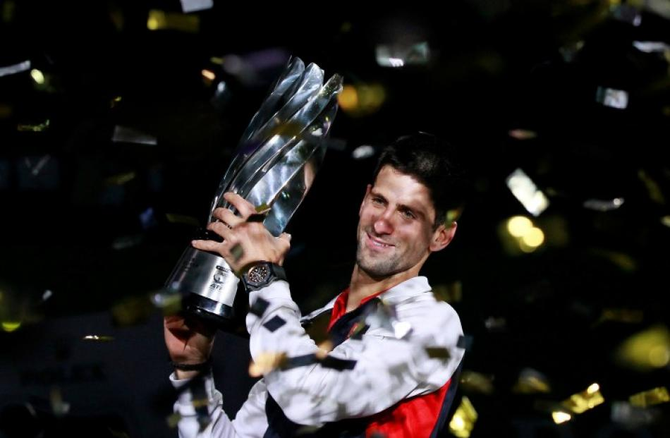 Novak Djokovic of Serbia celebrates with his trophy after beating Andy Murray of Britain to win...