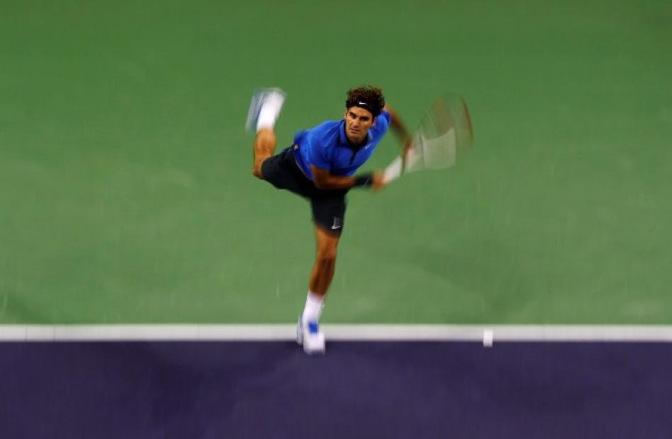 Roger Federer of Switzerland serves to Andy Murray of Britain during their men's singles...