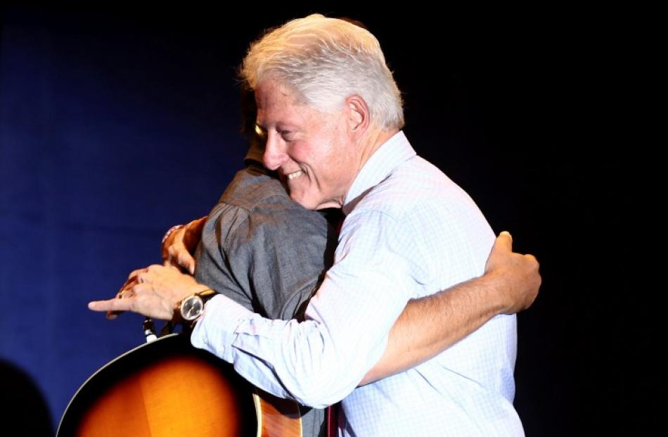 Musician Bruce Springsteen (L) gets a hug from former US president Bill Clinton at a concert...