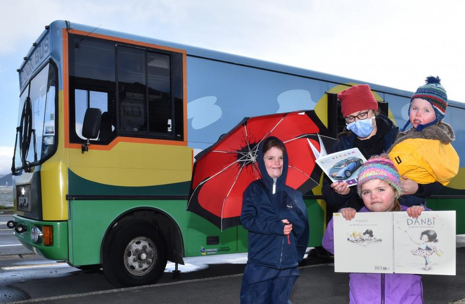 Enjoying a trip to the book bus on the first day of Alert Level 2 are Aliyah (7, left), Sarah,...