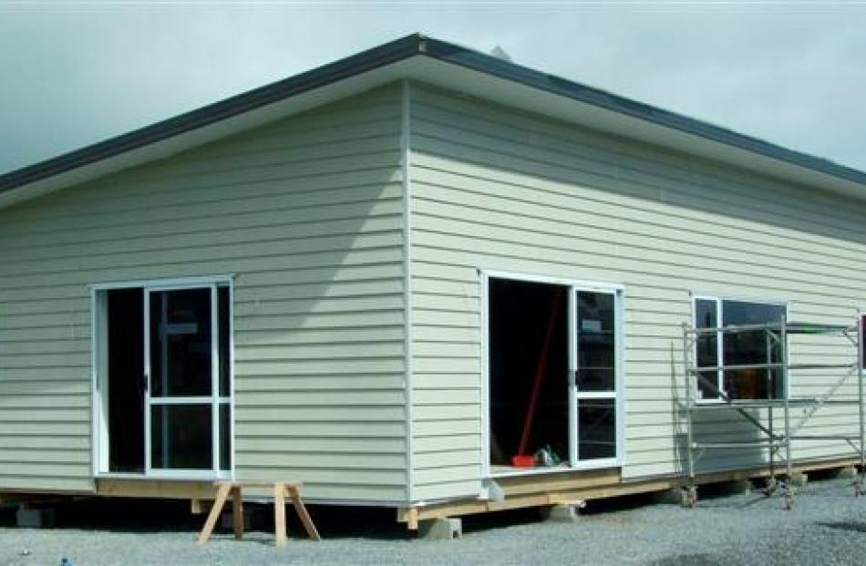 The house yesterday,  with  windows and doors installed and cladding up on the walls.