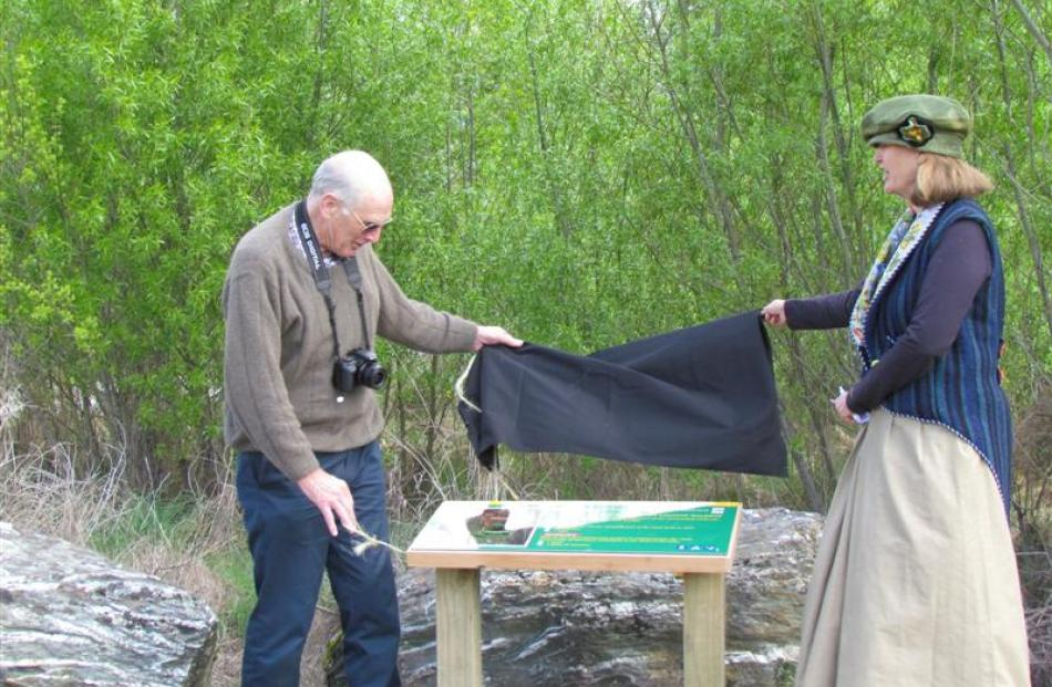 Pat Gollop  and Amanda Hasselman  uncover an information board for the Glenorchy Lagoon Walkway.