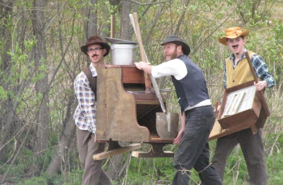 Actors in the re-enactment of the discovery of gold move a sluice to the Arrow River on Saturday....
