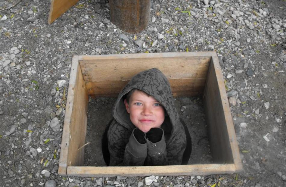 Luca Spring (7), of Arrowtown, plants himself inside the  hole  dug for the time capsule.