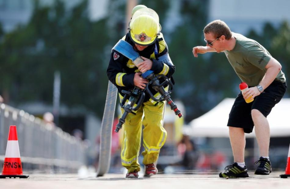 A teammate cheers on a firefighter from South Africa as he competes in the Toughest Firefighter...