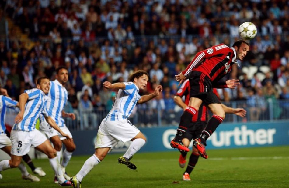 AC Milan's Giampaolo Pazzini (R) heads the ball next to Malaga's Manuel Iturra (C) during their...