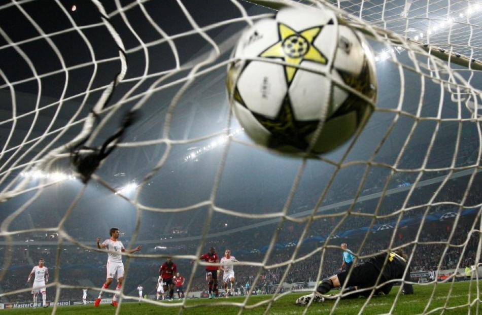 Bayern Munich's Thomas Muller (2nd L) scores a penalty against Lille during their Champion's...