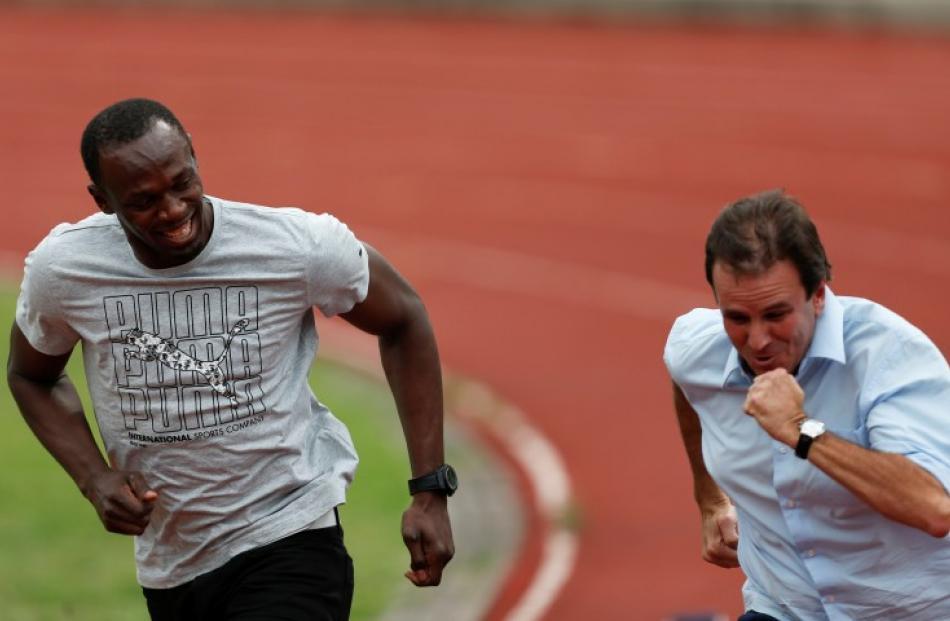 Jamaican Olympic gold medallist Usain Bolt (L) runs with Rio de Janeiro's Mayor Eduardo Paes at...