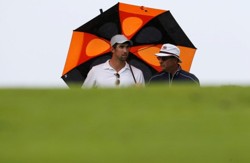 US Olympic swimmer Michael Phelps (L) talks to actor Andy Garcia during the first round of the...