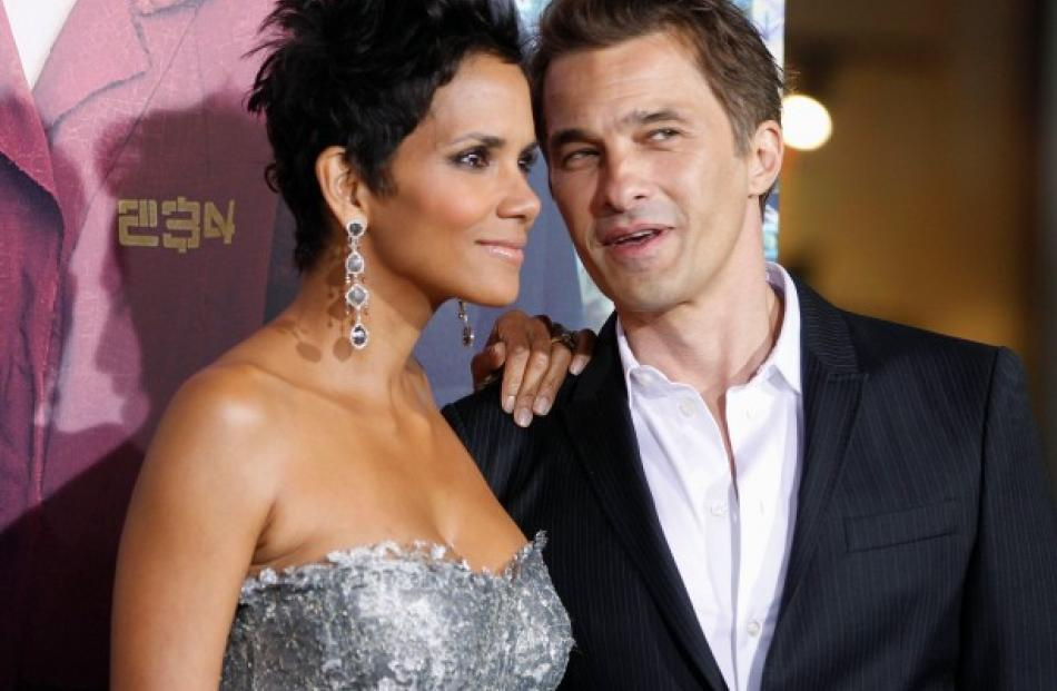 Actress Halle Berry poses as she arrives with her fiance, French actor Olivier Martinez, at the...