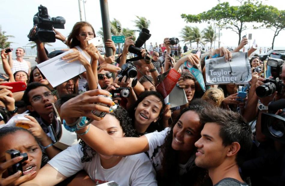 US actor Taylor Lautner poses for a picture with fans at a launch of the film 'A saga crepusculo:...