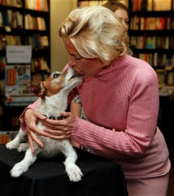 A fan receives a kiss from Uggie, the canine star of the movie 'The Artist', during the signing...