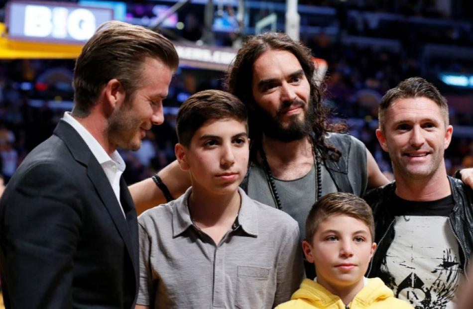 Footballer David Beckham (L) and actor Russell Brand (3rd L) pose for a photo with unidentified...