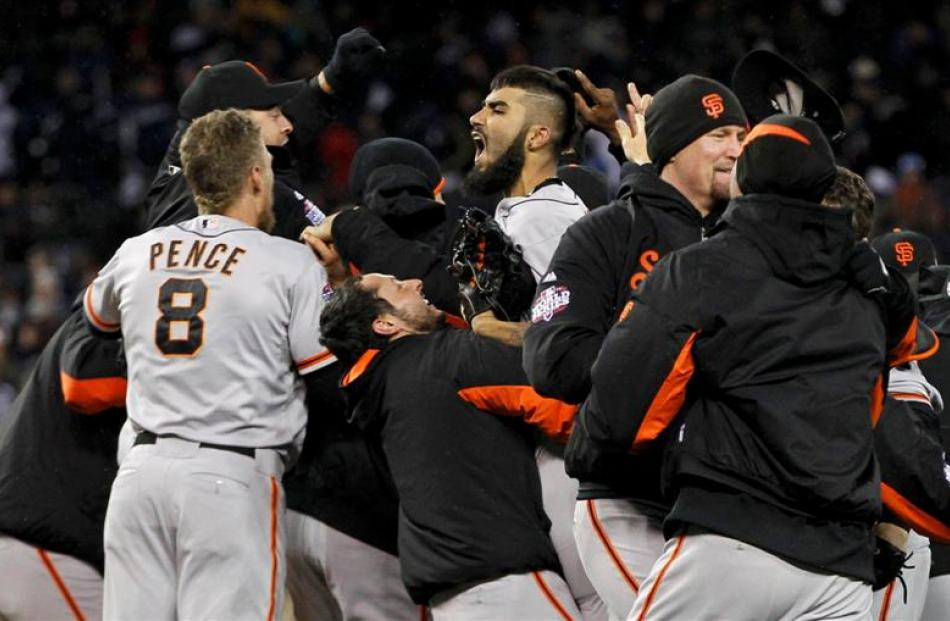 San Francisco Giants players surround relief pitcher Sergio Romo as they celebrate after winning...