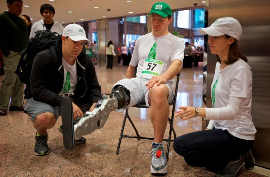 Research scientists Levi Hargrove (L) and Annie Simon watch as Vawter tests the leg before...