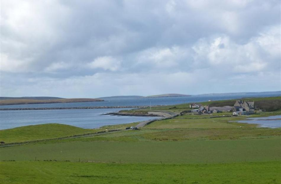 Green paddocks and grey buildings are staples of the Orkney landscape.