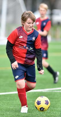 Cromwell and Alexandra's Blake Wallis (13) looks to kick the ball against Gore Wanderers.