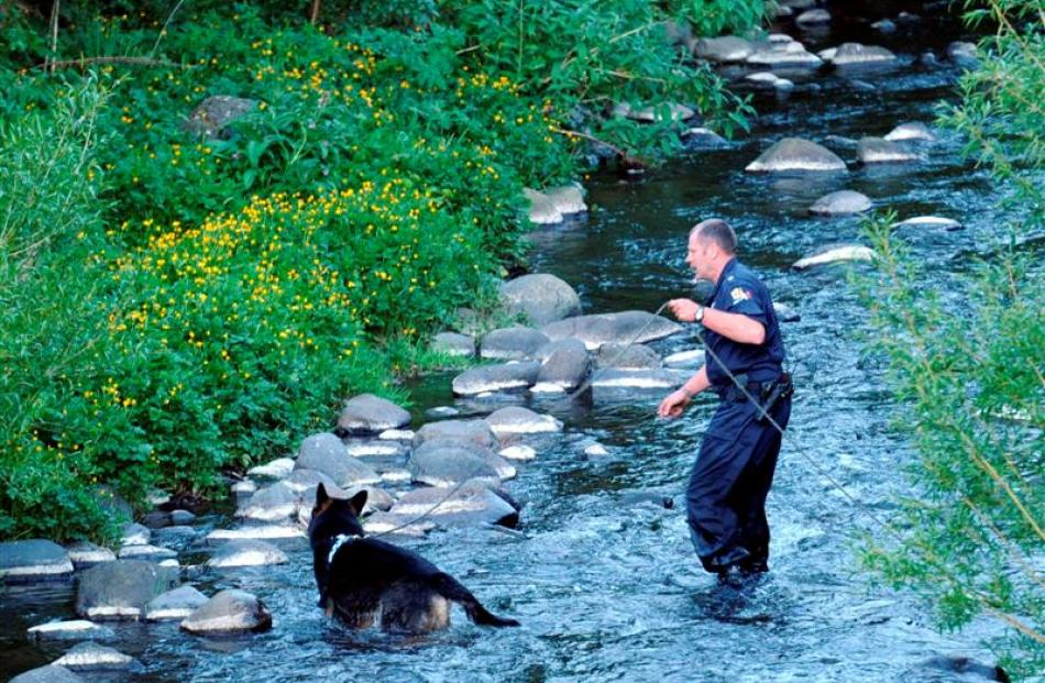 Senior Constable Peter Hanlin, of Dunedin, and his dog search the Water of Leith for a wanted man...