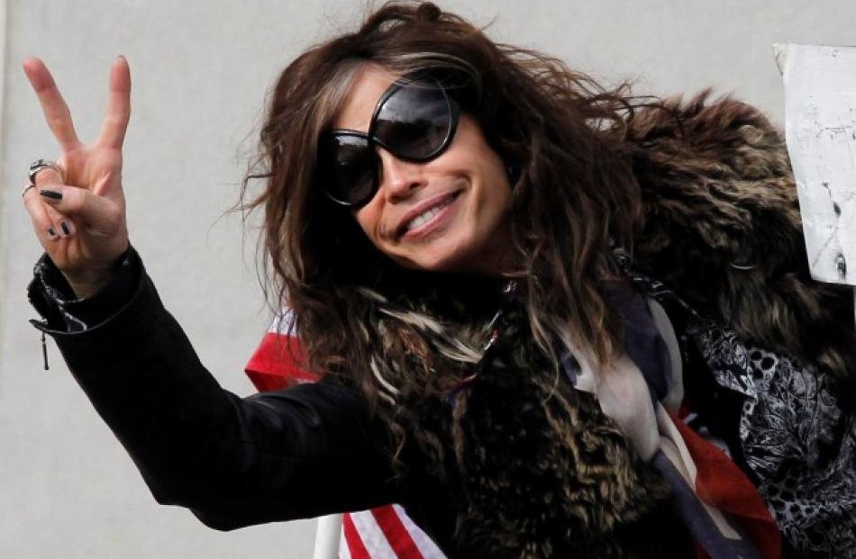 Aerosmith's Steven Tyler flashes a peace sign before the band's performance in Boston,...