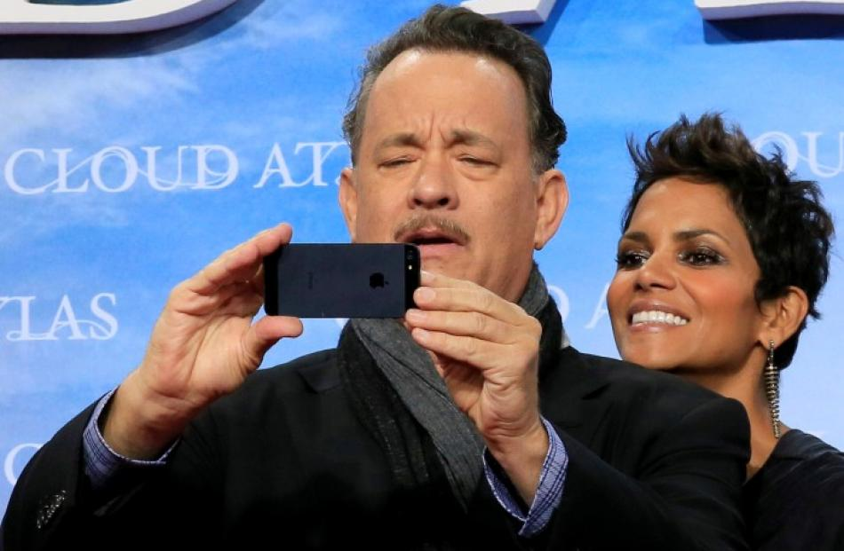 Cast members Tom Hanks and Halle Berry pose on the red carpet for the premiere of 'Cloud Atlas'...