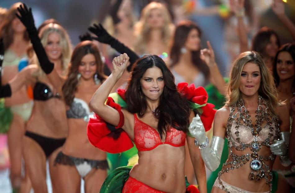 Model Adriana Lima (front L) walks with other models as they present creations during the...