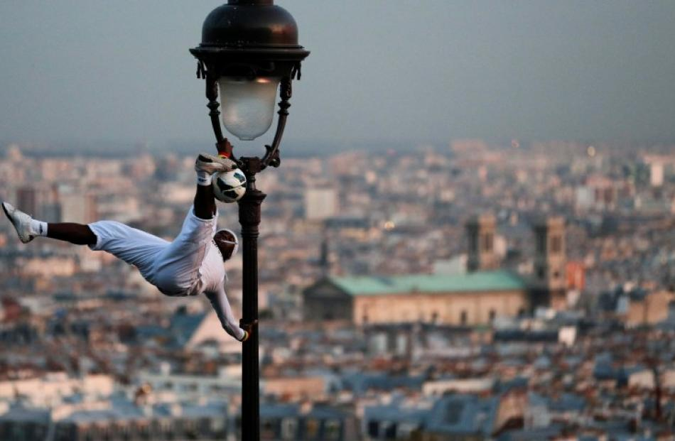 A football freestyler performs on a light pole next to the Sacre Coeur Basilica in Paris. REUTERS...