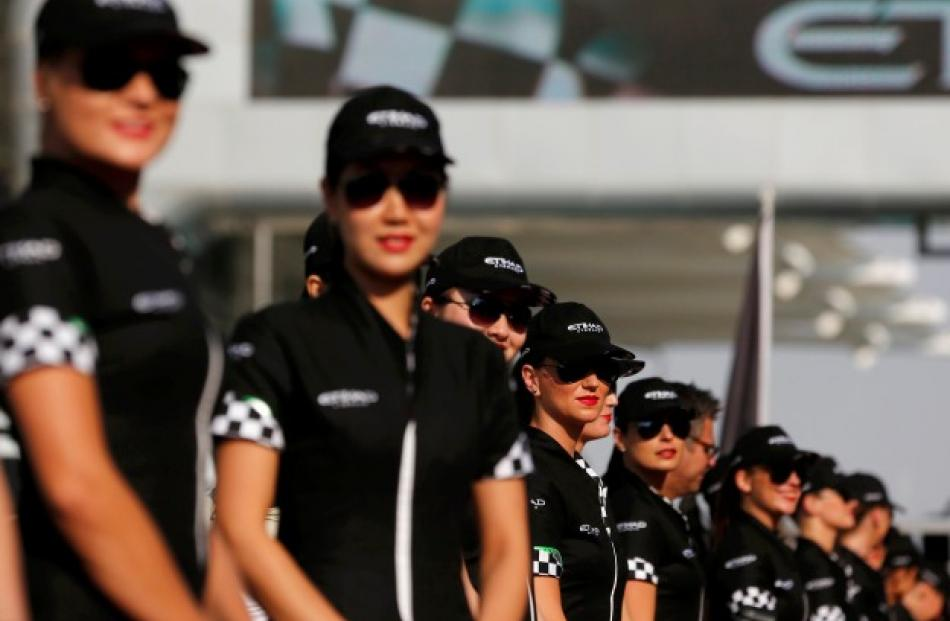 Grid girls pose before the Abu Dhabi F1 Grand Prix at the Yas Marina circuit on Yas Island....