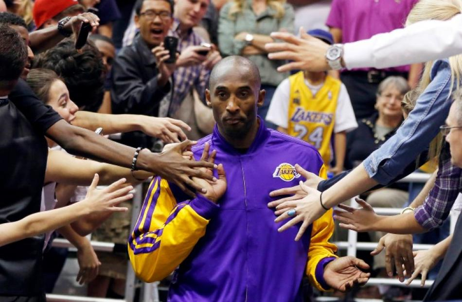 Los Angeles Lakers guard Kobe Bryant walks past fans before the second half of their NBA...