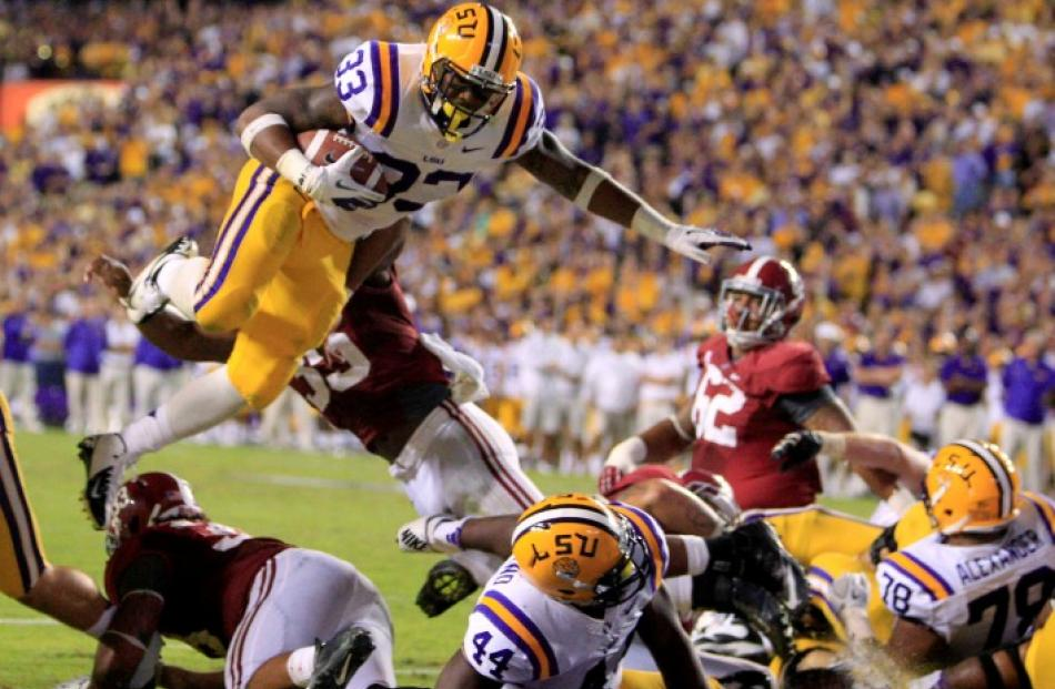 LSU Tigers running back Jeremy Hill (33) leaps over Alabama Crimson Tide defenders while scoring...