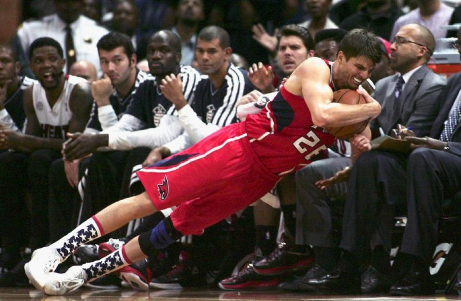 Atlanta Hawks guard Kyle Korver falls on to the Miami Heat bench during their NBA basketball game...